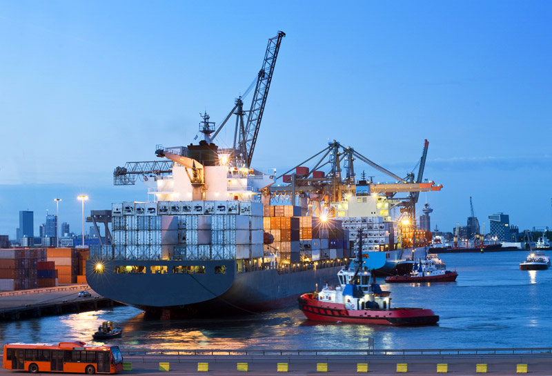 Several-tugs-and-support-vessels,-assisting-a-huge-container-ship